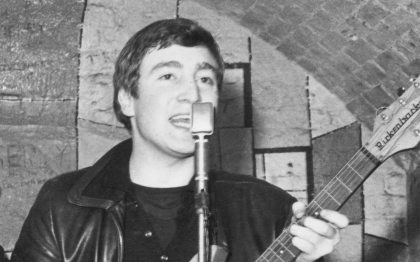 December 1961: Singer, guitarist and songwriter John Lennon (1940 - 1980) of the British group The Beatles live on stage at the Cavern Club in Matthew Street, Liverpool. (Photo by Evening Standard/Getty Images)